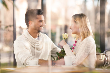 Young couple with a white rose sitting in a restaurant