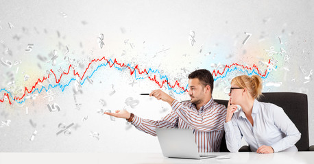 Business man and woman sitting at table with stock market graph