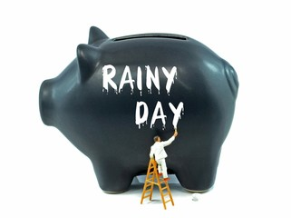 Saving for a rainy day financial concept on a black piggy bank