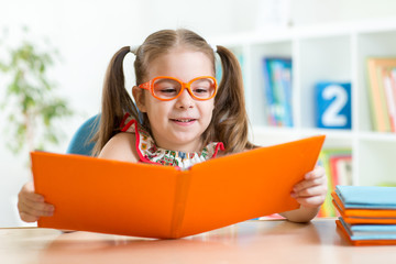 Happy funny child girl in glasses reading a book in primary
