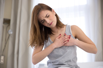 Young woman in pajamas having heart attack