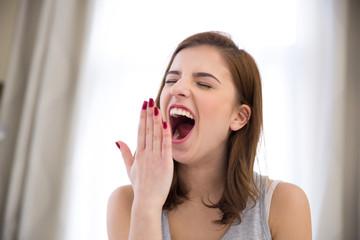 Young beautiful woman yawning at home