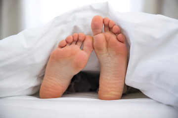 Feet of a young woman on the bed