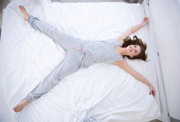 Portrait of a happy woman lying on the bed in star pose