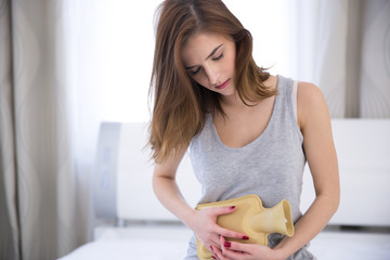 Young woman with hot water bottle on stomach on the bed