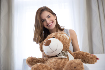 Portrait of pretty young woman with teddy bear