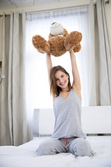 Portrait of happy cute woman sitting on the bed with teddy bear