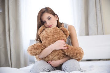 Beautiful young woman sitting on the bed with teddy bear