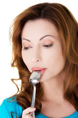Portrait of young woman with spoon in her mouth