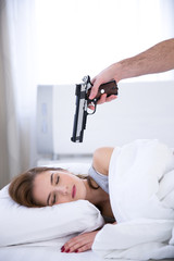 Young woman sleeping while the gun aimed at her