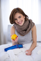 Portrait of a sick woman holding lemon on the bed