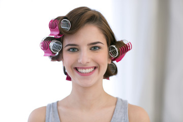 Portrait of a smiling woman with curlers on her head