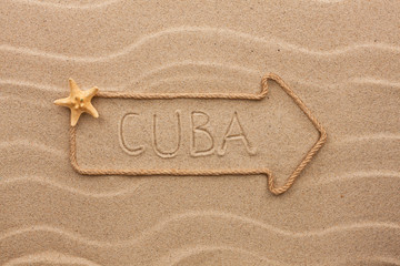 Arrow made of rope and sea shells with the word Cuba on the sand