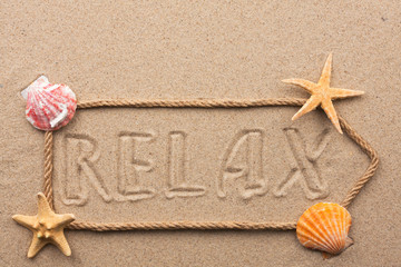 Arrow made of rope and sea shells with the word relax on the san