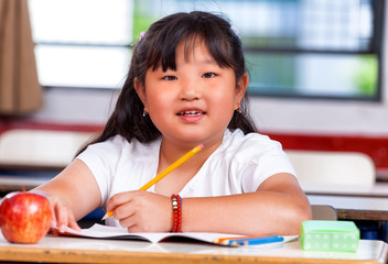Pretty asian girl at elementary school writing on her book
