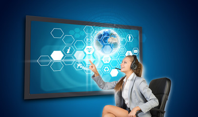 Businesswoman in headset pressing touch screen button on virtual
