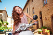 Young beautiful italian woman sitting on a italian scooter.
