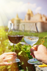 Two hands holding wineglasses against Chateau d'Aigle, Switzerla