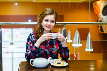 thoughtful beautiful girl in a plaid shirt drinking tea in a caf
