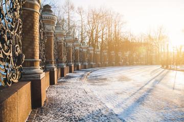Sunlit snowy street. The railing of Michael (Mikhaylovsky) Garde
