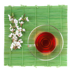 Japanese green tea and sakura branch over bamboo mat