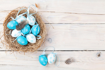 Easter background with blue and white eggs in nest