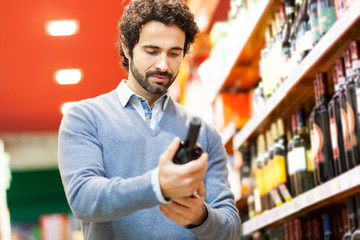 Man in a supermarket choosing a wine bottle