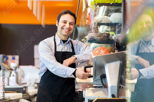 Leinwanddruck Bild Shopkeeper cutting ham in a grocery store