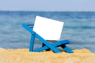 blank board on deckchair on the beach as summer