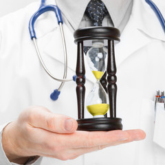 Medical doctor and hourglass - heath care concept