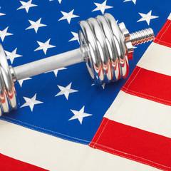 Metal dumbbell over US flag - studio shot