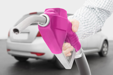 Pink color fuel pump gun in hand with car on background