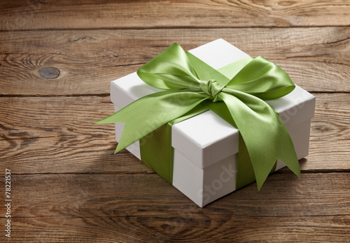 Beautiful gift box with a bow on the table from the old boards - 78221537