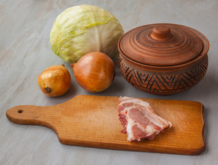A piece of raw pork on a cutting board and vintage clay pot and