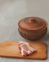 A piece of raw pork on a cutting board and vintage clay pot