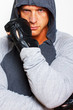 Serious guy in special gloves is posing on a white background