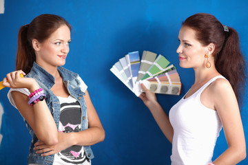 Two Young beautiful women holding color palette , standing near