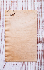 old blank sheet of paper on wooden board with copyspace for your