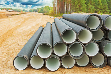 pile of big water pipes on construction site