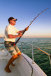 Angler fisherman fighting big fish on the ocean from the boat