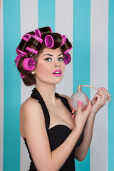 retro pin up girl spraying perfume with hair rollers