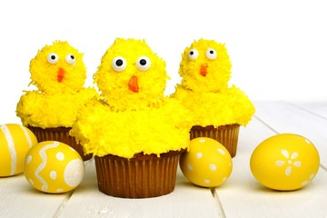 Spring chick cupcakes on white wood with Easter eggs