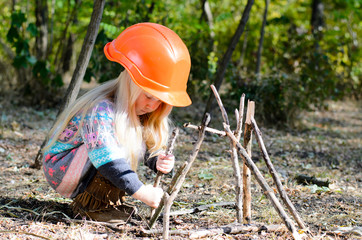 Girl With Helmet Assembling Sticks on the Ground
