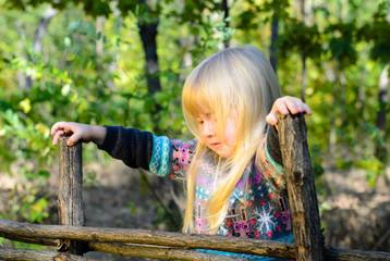 Blond Girl Playing at the Wooden Garden Fence
