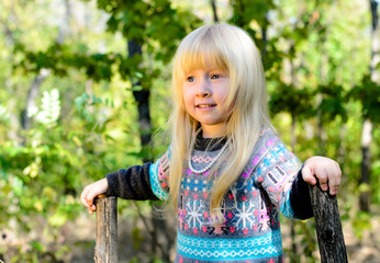 Smiling Little Blond Girl Playing at the Garden