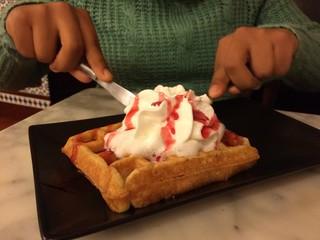 mujer disfrutando un delicioso wofre con nata de postre