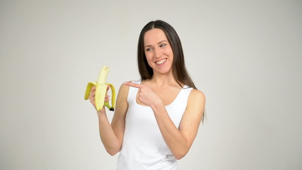 young beautiful woman eating a banana and shows thumb