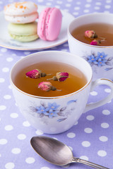Cups of herbal tea with macaroons on polka dot towel