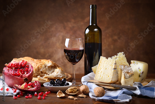 Fotobehang Wijn Red wine, cheese, walnuts, olives, pomegranate and bread