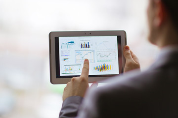 analyzing financial statistics displayed on the tablet
